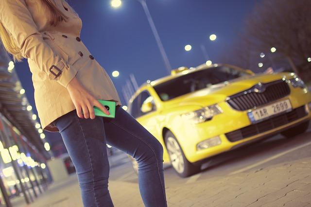 žena před taxíkem